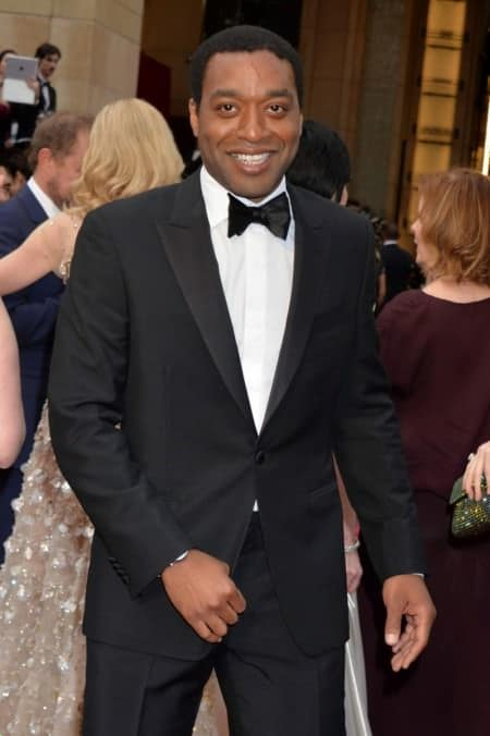 Chiwetel Ejiofor in single breasted peak lapel tuxedo in black with turndown collar shirt & wristwatch