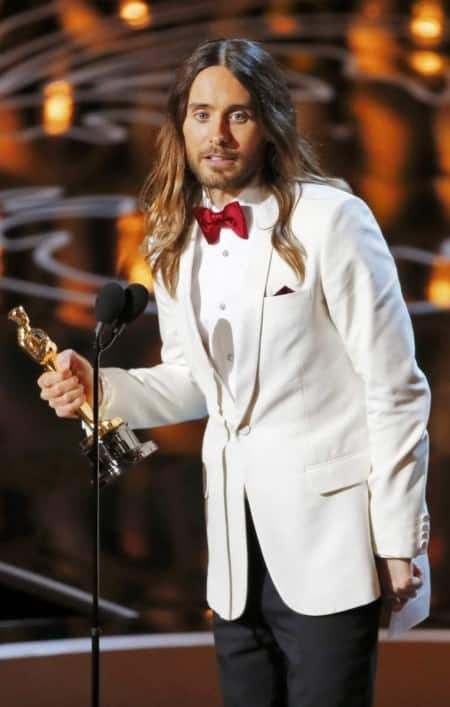 Jared Leto on stage, showing off is white dinner jacket, studs and pre tied bow tie in red