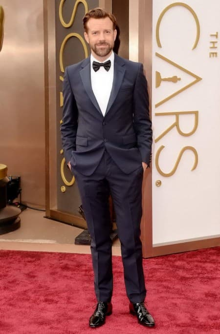 Jason Sudeikis in a notched lapel tuxedo with flap pockets by Prada, turndown collar & pre tied bow tie with black patent leather oxfords