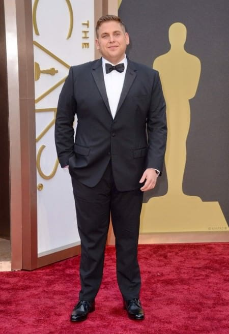Jonah Hill in notched lapel tuxedo with flapped pockets, wristwatch and derby shoes