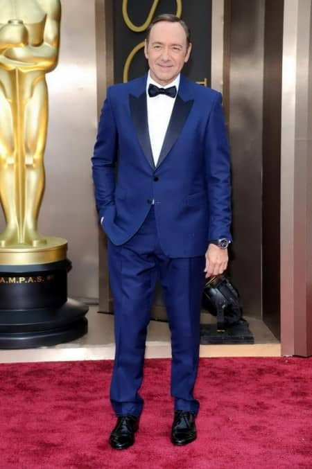 Kevin Spacey in dark blue tuxedo with flapped pockets, pre tied bow tie, no cummerbund, wristwatch & black derby shoes