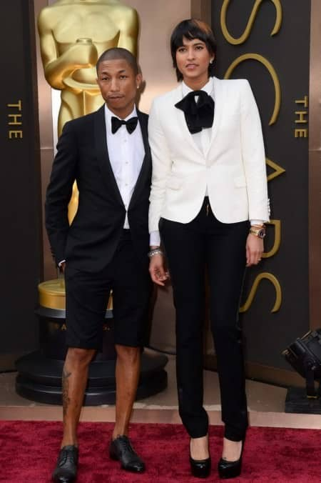 Pharrell Williams in slim shawl collar tuxedo with double button, 4 gold shirt studs, no cummerbund black shorts and captoe derbies in black
