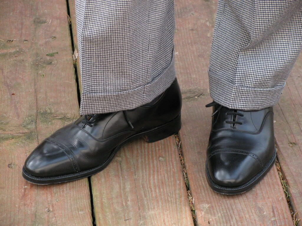 Houndstooth trousers with cuffs, which is a bit informal for a stroller, with quarter brogue oxfords in black