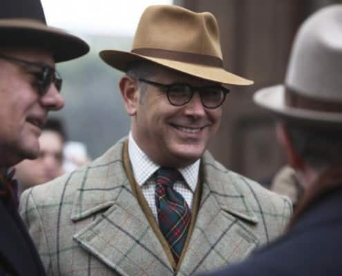 Plaid Ulster overcoat with Tattersall shirt, tartan tie, with snap brim fedora and silm hat band
