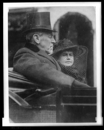 Woodrow Wilson and wife riding in back seat of a carriage to second inauguration with top hat and velvet collar on March 5, 1917