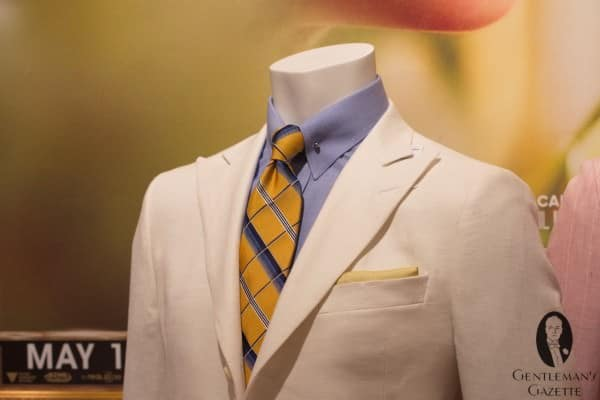 White herringbone linen suit with blue shirt and collar bar
