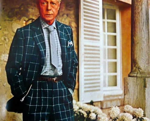 DoW in chalk stripe windowpane suit checked shirt and short silver tie with end tucked into waistband with brown leather belt
