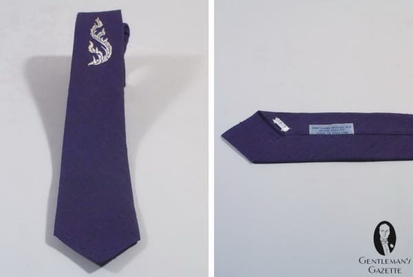 Hand woven Shantung silk in dark blue made into a tie with white embroidery