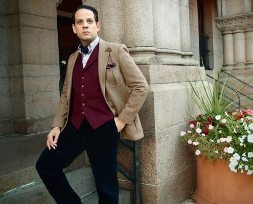 Brown tweed jacket with burgundy odd vest, ascot & navy corduroy pants