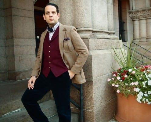 Brown tweed jacket with burgundy odd vest, ascot & navy corduroy pants
