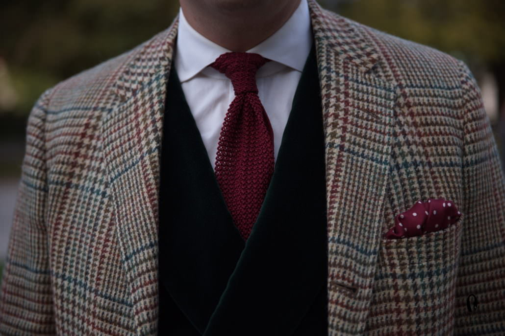 Green Vest with red knit tie and burgundy polka dot pocket square with prince of wales check tweed