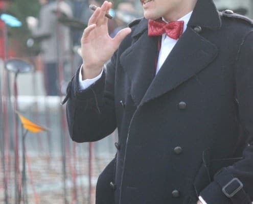 Cigar with double breasted overcoat and frayed edges paired with a red quilted leather bow tie