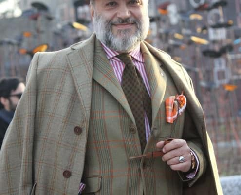 Gianni Fontana in an outfit dominated by green plaids. Just the jacket or the coat work well but not both together