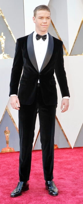 Will Poulter in shawl collar 1 button dinner jacket without vest or cummerbund and sneaker style tucked-in shoelaces