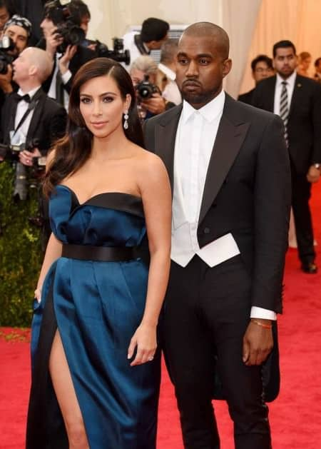 Kanye West in ill fitting tailcoat without a bow tie or studs but pants that are so tight they wrinkle