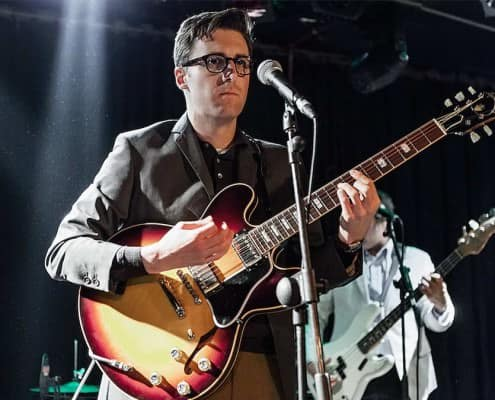 Nick Waterhouse in action wearing a gray slim lapel jacket with 2 cuff buttons