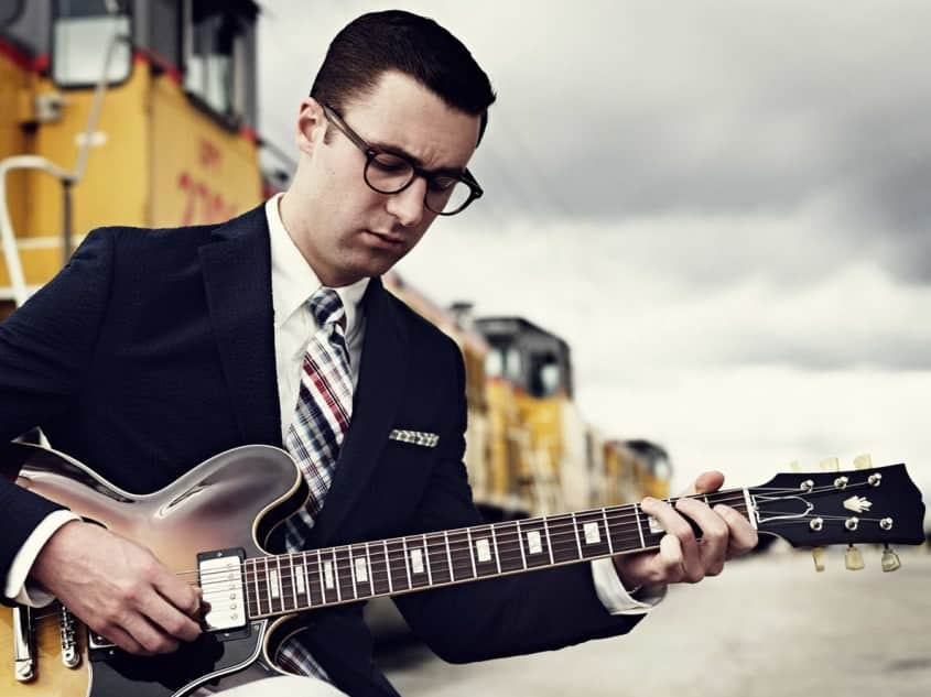 Nick Waterhouse with navy seersucker sport coat, oxford cloth button down shirt & Madras tie