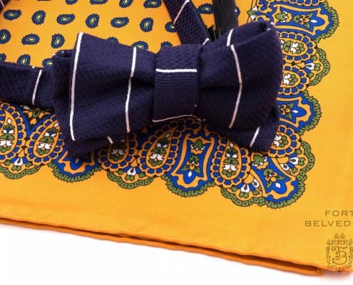 Vertical striped navy jacquard bow tie. with yellow orange paisley pocket square by Fort Belvedere