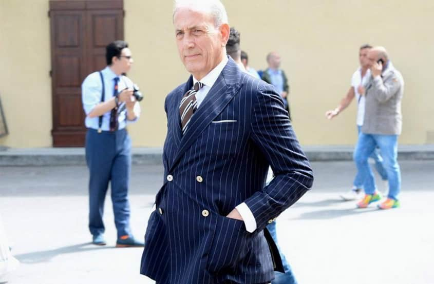 Seasoned Gentleman in navy striped suit with triple stripe tie