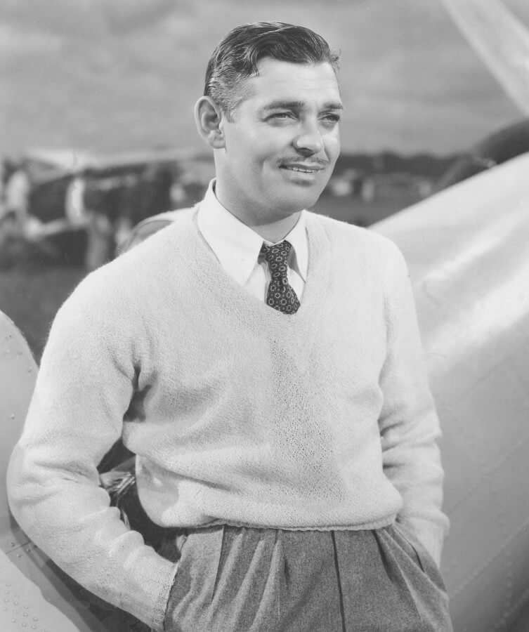 Clark Gable wearing a v-neck sweater and a printed tie micropattern tie with grey pleated high rise pants