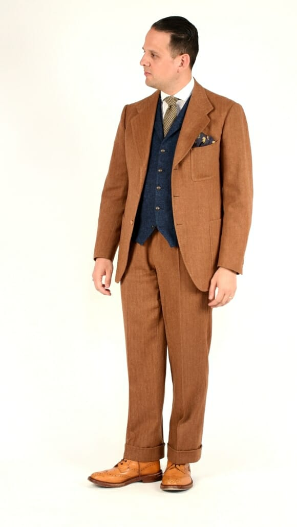 Sven Raphael Schneider wearing a rust-colored, single-breasted herringbone suit with a contrasting vest and tan full brogue boots