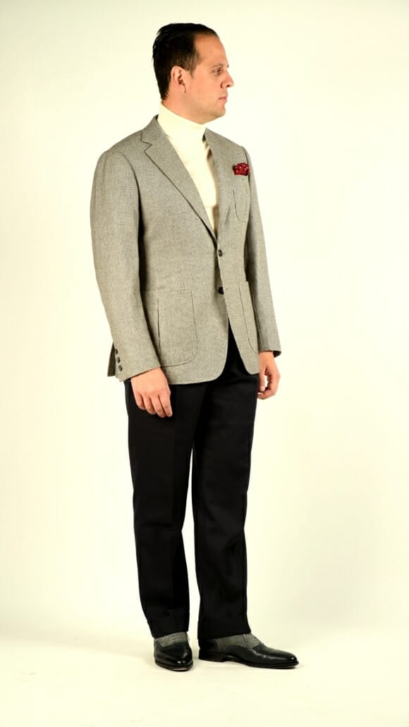 Sven Raphael Schneider wears a patch pocket sports coat with a turtleneck, navy trousers and navy and gray suede u-cap brogues