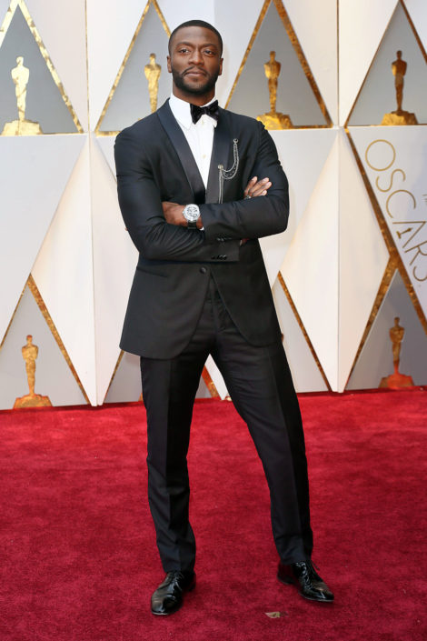 Aldis Hodge in Armani slim shawl collar tuxedo with huge, showy wristwatch and lapel chains
