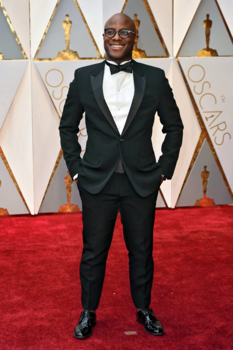Barry Jenkins with big smile and flap pocket tux without cummerbund but rounded wing collar and no socks