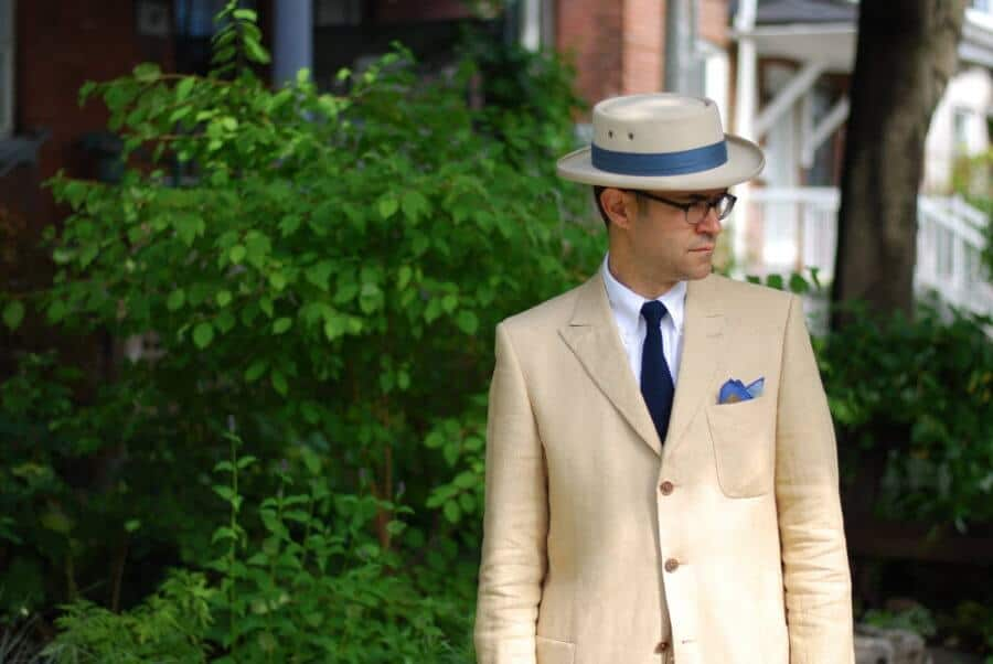 Pedro Mendes with dark blue knit tie, white button down shirt and ivory linen suit with crown fold pocket square - note the unusual hat