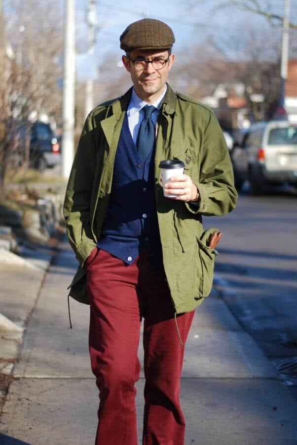 Pedro during fall autumn season wearing red slacks, blue knit cardigan, green madder tie, striped shirt and olive green jacket