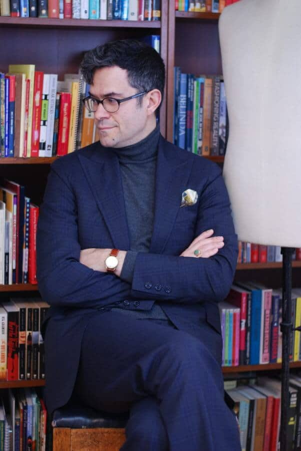 Pedro in dark suit with grey turtleneck sweater, wristwatch and signet ring