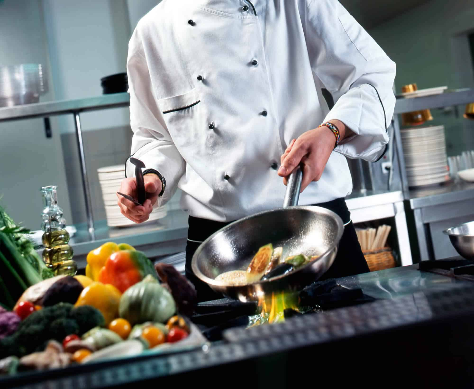A chef using his cookware in the kitchen