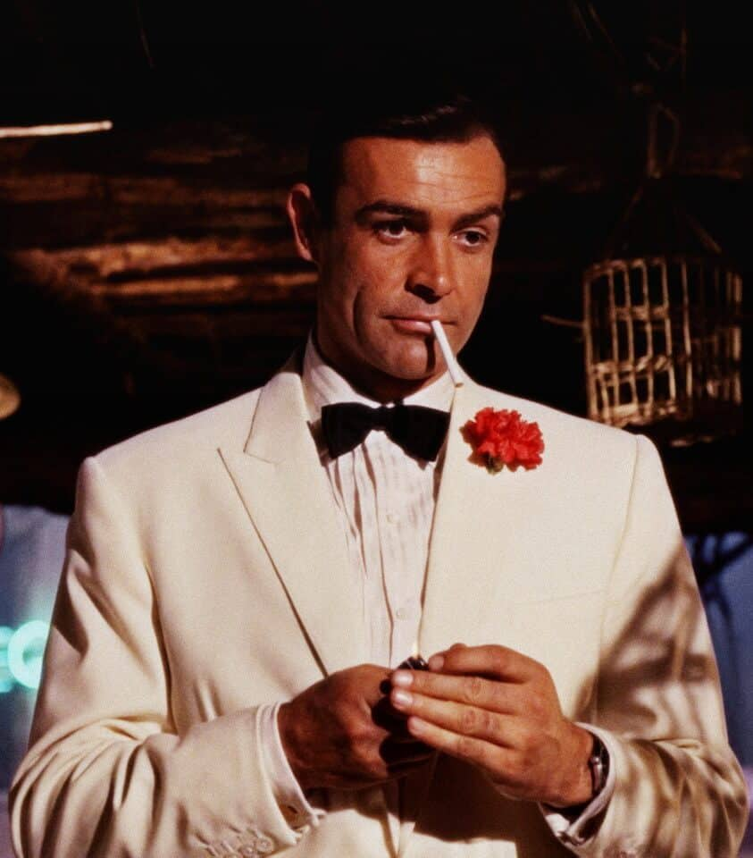 Sean Connery as James Bond wearing a white dinner jacket with a red carnation boutonniere