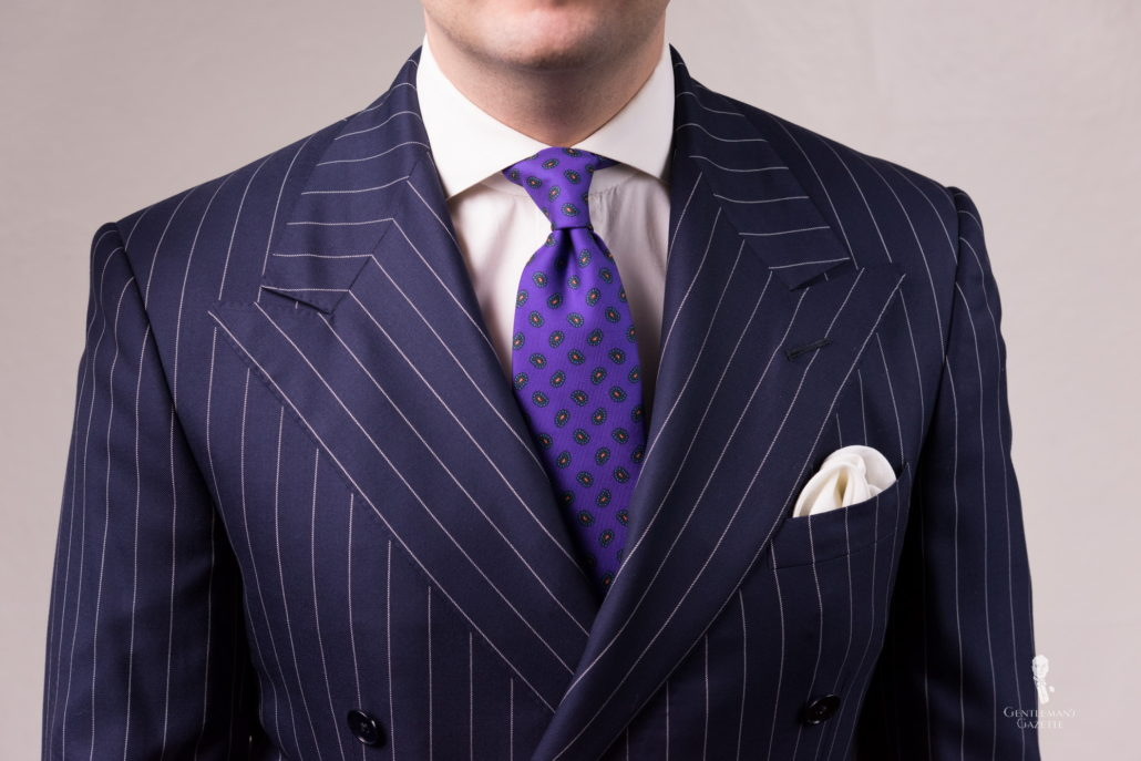 Navy patterned suit paired with a white dress shirt, Madder Silk Tie in Purple with Paisley Fort Belvedere and white pocket square