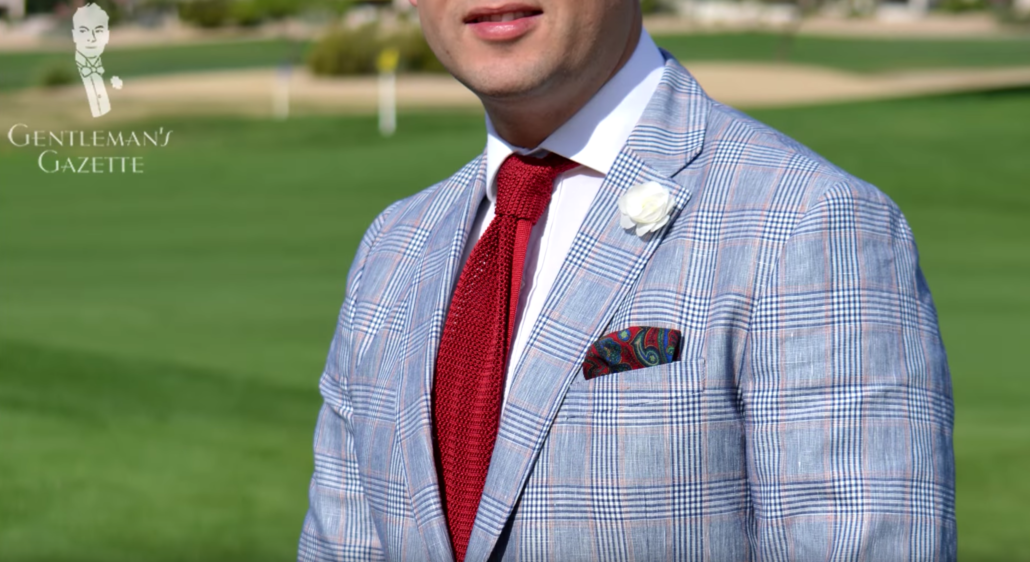 Raphael wearing a Gagliardi Glen check Summer Sportcoat with Knit Tie in Solid Red Silk, White Spray Rose Boutonniere and Pocket Square from Fort Belvedere