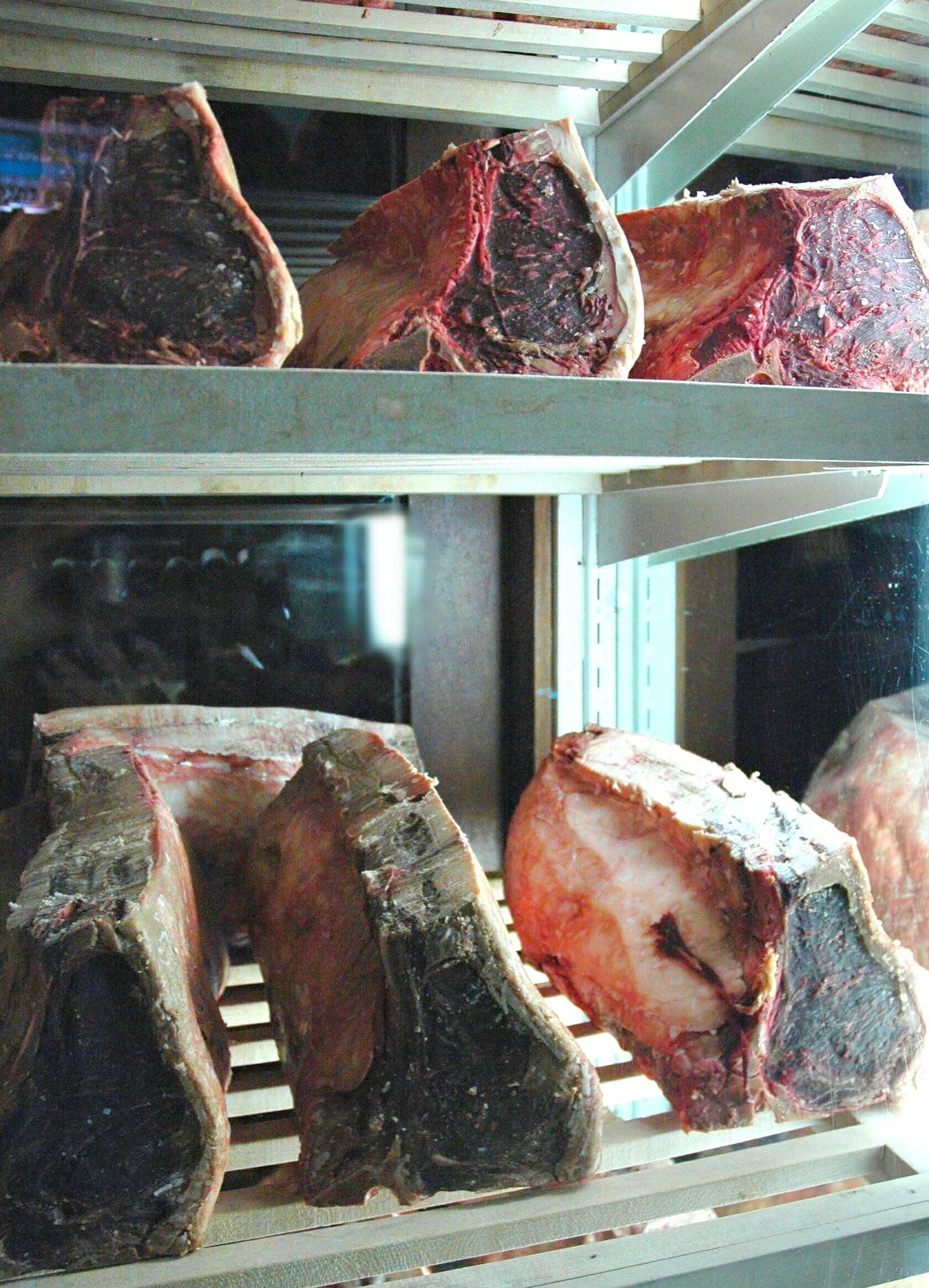 A selection of dry-aged cuts of beef. Note the dark and textured exterior.