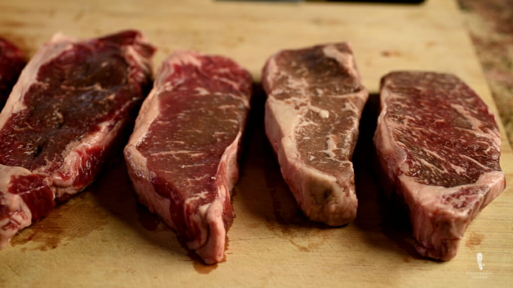 New York Strip aka Kansas City Strip Steak cuts with different degree of marbling - From Right to Left - Akaushi, Prime, Select, Grass Fed