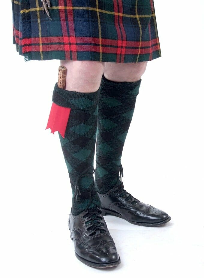 Diced kilt hose with garter flashes. The shoes are ghillie brogues