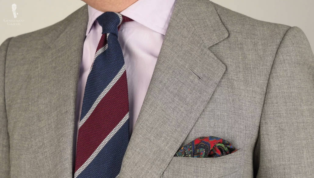 A Cashmere-Wool Grenadine Tie in Dark Blue, Burgundy, Light Grey Stripe from Fort Belvedere, paired with a light gray suit, lavender shirt, and patterned pocket square