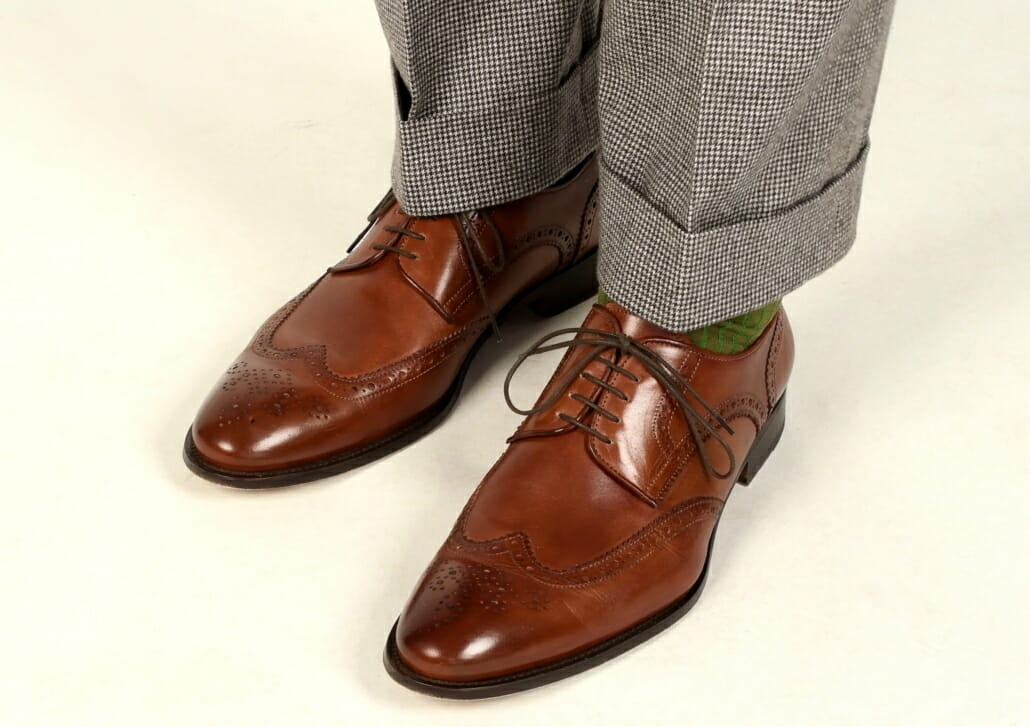 Brown calf leather full brogue Wingtips by Ace Marks paired with houndstooth suit and brown and green shadow stripe socks from Fort Belvedere