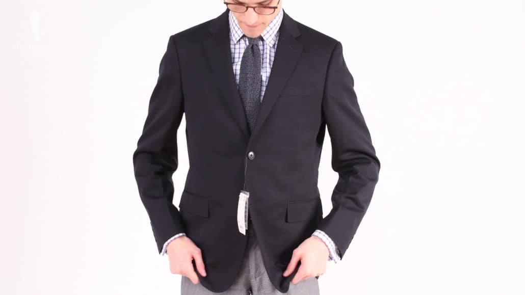 Preston trying on a navy suit jacket from Uniqlo.