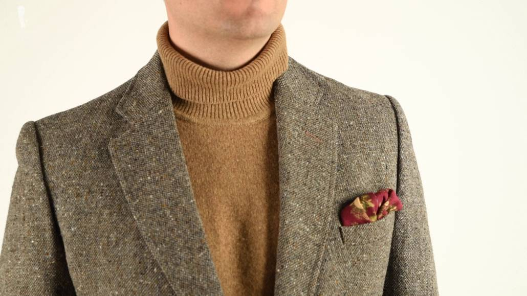 A silk-wool pocket square with an animal motif paired with a tweed jacket and a turtleneck sweater.