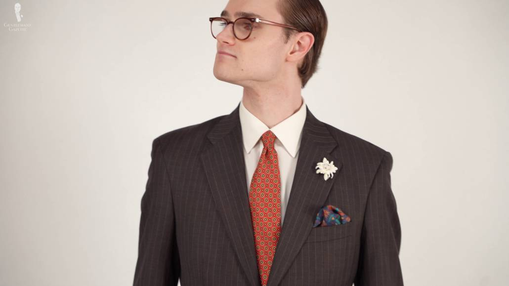Preston in a dark brown patterned suit jacket, white collared shirt, and accessories from Fort Belvedere.