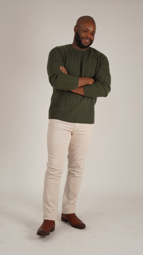 Kyle;  at the age of 30, wearing a green cable-knit sweater, cream jeans and a brown braided leather boot.