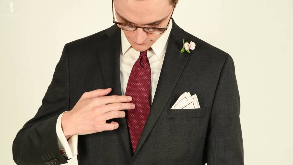 A gray suit paired with a red pin dot tie, white collared shirt, a white pocket square and a white pocket square.