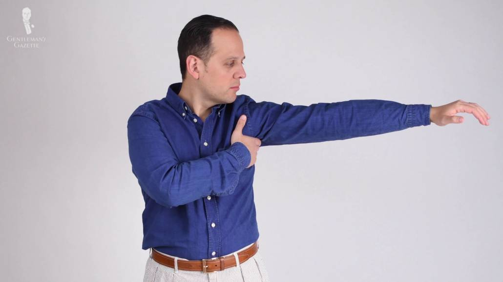 Raphael wearing a blue Eton dress shirt and stretching his arms.