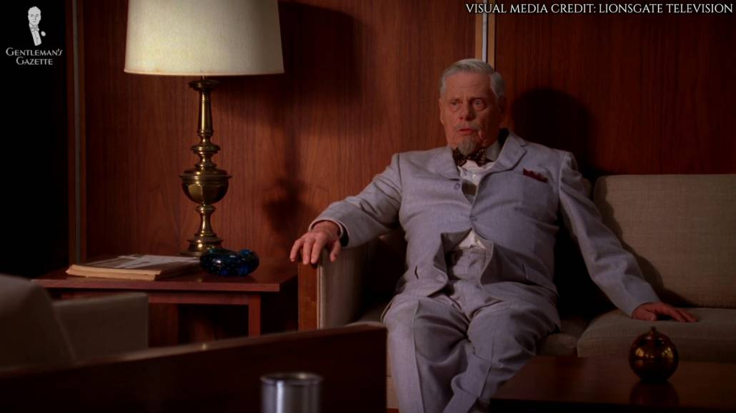 Bertram Cooper in taupe-colored suit with contrasting elements. He wears a blue and purple gingham shirt, which would not have been quite office-appropriate at the time. He also wears a speckled navy or bluish bow tie and a blue pocket square.