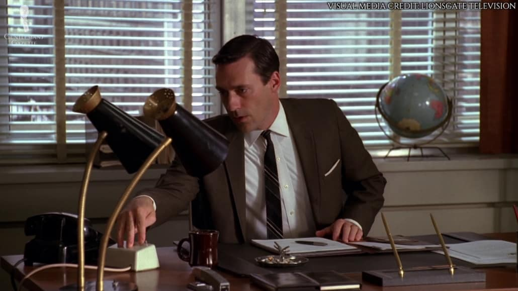 Don Draper in a dark brown suit jacket, a stripe patterned tie in dark colors, white wing collared shirt, and a white pocket square in TV fold.