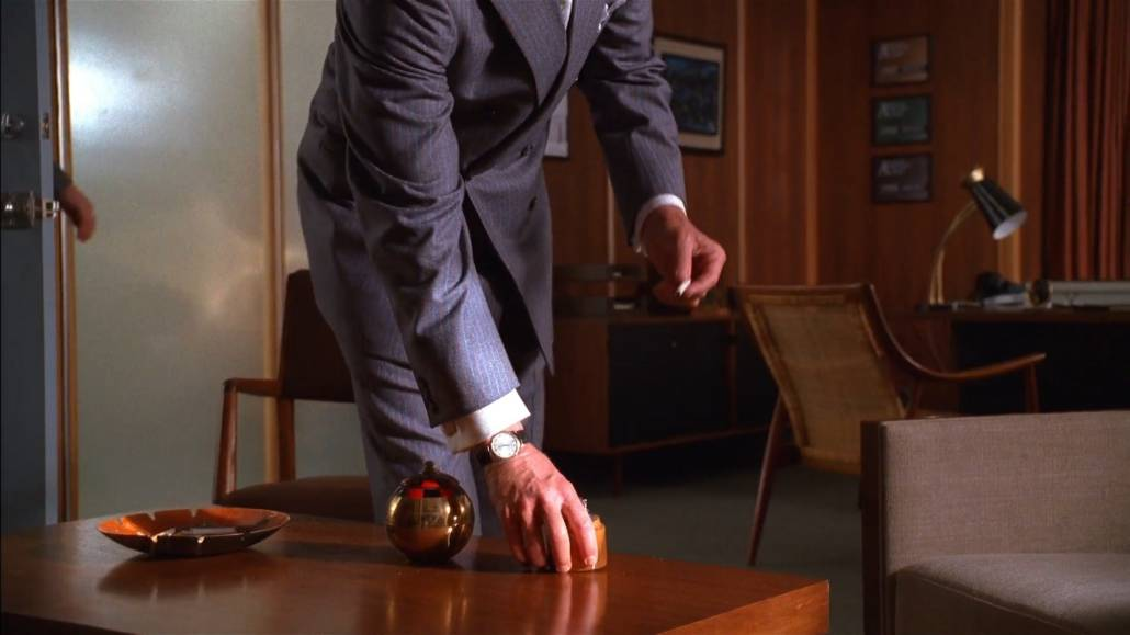 Don Draper sporting a French cuff and gunmetal cufflinks. He's also donning a pin-striped gray business suit.