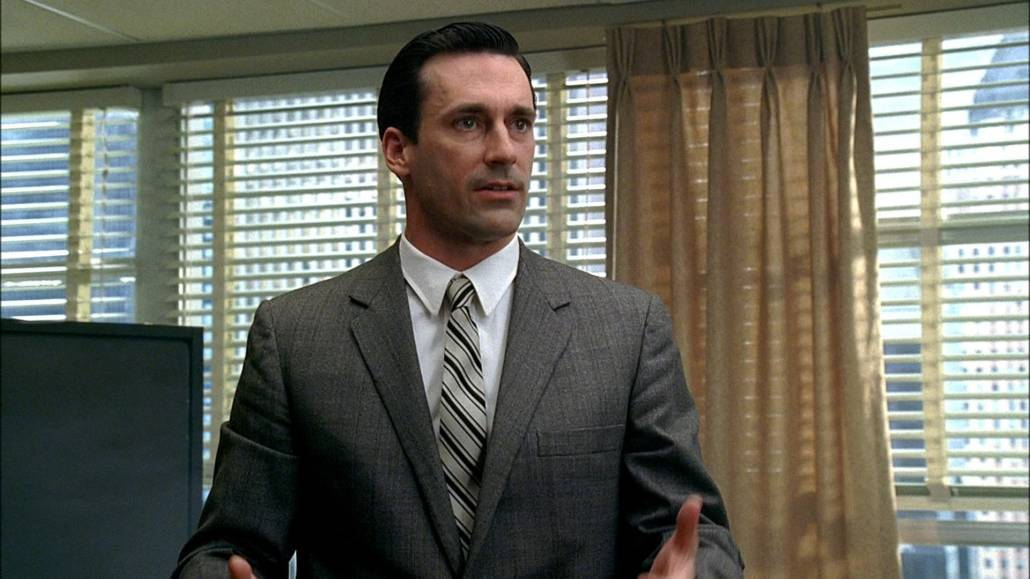 Don Draper in a light gray suit, striped tie, and white dress shirt
